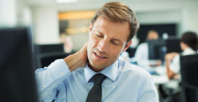 Businessman rubbing his neck in office